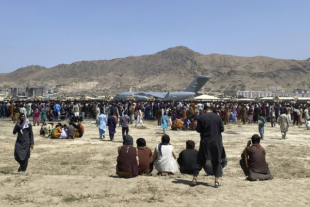 Hundreds of people gather near a U.S. Air Force C-17 transport plane at a perimeter at the international airport in Kabul, Afghanistan, Monday, August 16, 2021. On Monday, the U.S. military and officials focus was on Kabul's airport, where thousands of Afghans trapped by the sudden Taliban takeover rushed the tarmac and clung to U.S. military planes deployed to fly out staffers of the U.S. Embassy, which shut down Sunday, and others. (Photo by Shekib Rahmani/AP Photo)