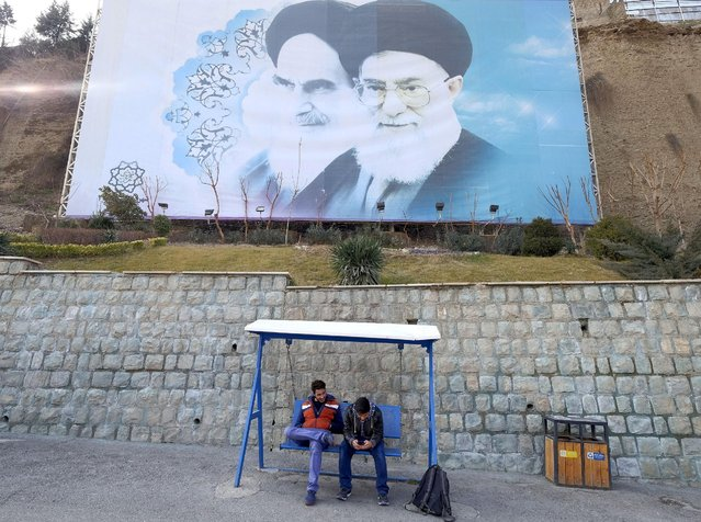 Iranian youths sit under a large picture of Iran's late leader Ayatollah Ruhollah Khomeini (L), and Iran's Supreme Leader Ayatollah Ali Khamenei at a park in Tehran, Iran, in this January 17, 2016 file photo. (Photo by Raheb Homavandi/Reuters/TIMA)