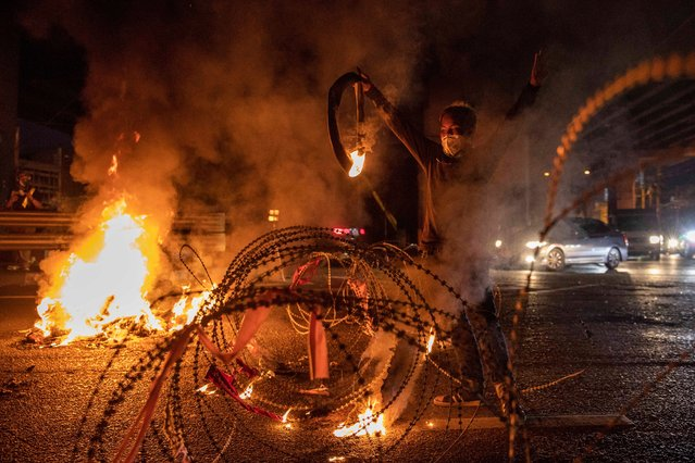 Thai anti-government activists light tires on fire during at the Din Daeng Intersection during a rally on September 06, 2021 in Bangkok, Thailand. Anti-government protesters have continued to hold rallies for weeks, often clashing with police, despite Covid-19 cases remaining at record highs. (Photo by Lauren DeCicca/Getty Images)