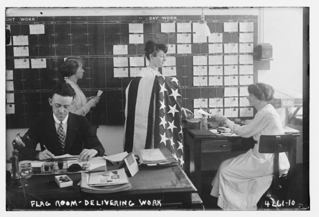 A man and women, one holding an American flag, work in an office at the Brooklyn Navy Yard, Brooklyn, New York, July 7, 1917, in this Library of Congress handout photo. (Photo by Reuters/Bain Collection/Library of Congress)