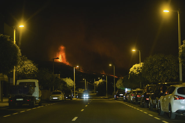 Lava flows from an eruption of a volcano near El Paso on the island of La Palma in the Canaries, Spain, in the early hours of Monday, September 20, 2021. Lava continues to flow slowly from a volcano that erupted in Spain's Canary Islands off northwest Africa. The head of the islands' regional government says Monday he expects no injuries to people in the area after some 5,000 were evacuated. (Photo by Jonathan Rodriguez/AP Photo)