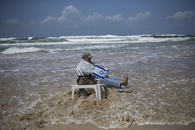 John Voracek sits on a chair in the Mediterranean sea as he waits for Israeli Air Force planes to fly, during Israel's 67th Independence Day, in Tel Aviv, Israel, Thursday, April 23, 2015. Israel is celebrating its annual Independence Day, marking 67 years since the founding of the state in 1948. (AP Photo/Ariel Schalit)