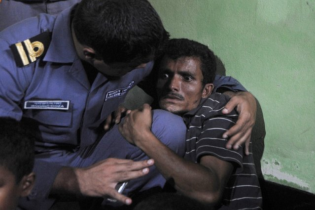 A Rohingya Muslim from Myanmar (R), who tried to cross the Naf river into Bangladesh to escape sectarian violence, cries  near his family in a Bangladeshi Coast guard station in Teknaf on June 19, 2012, before being sent back to Myanmar. (Photo by Munir Uz Zaman/AFP Photo)