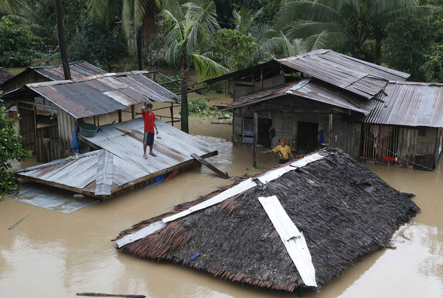 "A resident stands on the roof of his home that is submerged in heavy flooding brought by tropical depression ""Agaton"", in Butuan city on the southern Philippine island of Mindanao January 21, 2014. (Photo by Erik De Castro/Reuters)"
