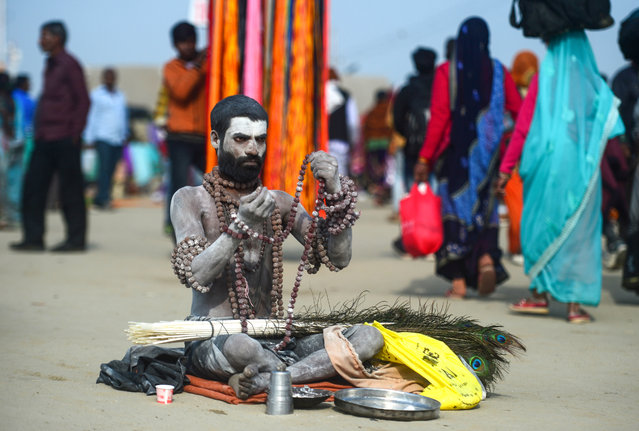 An Indian sadhu (Hindu holy man) sits on the banks of Sangam – the confluence of the Ganges, Yamuna and mythical Saraswati rivers – on the auspicious bathing day of 'Maghi Purnima' during the Kumbh Mela festival in Allahabad on February 19, 2019. Millions of Hindu pilgrims took the plunge in holy rivers on the most auspicious bathing days of the Kumbh Mela festival, led by naked, ash-smeared holy men and accompanied by chants from Hindu holy texts. (Photo by Sanjay Kanojia/AFP Photo)