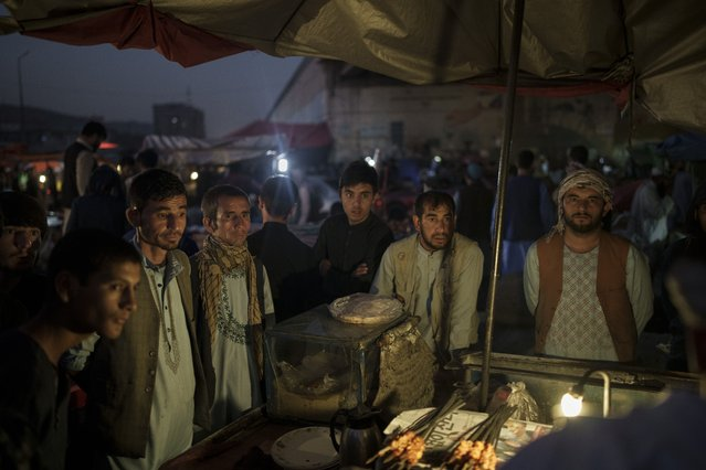 Afghans gather at a local market in Kabul, Afghanistan, Sunday, September 26, 2021. (Photo by Felipe Dana/AP Photo)