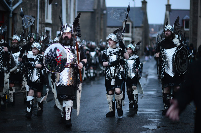 """Locals dressed as Vikings  march through the streets of Lerwick on January 28, 2014, in the Shetland Islands, Scotland. The traditional festival of fire is known as """"Up Helly Aa"""". The spectacular event takes place annually on the last Tuesday of January. The climax of the day comes with participants in full costume hauling a Viking longboat through the streets of Lerwick to the edge of town where up to 1000 people parade and throw their flaming torches into the galley. (Photo by Jeff J. Mitchell/Getty Images)"""