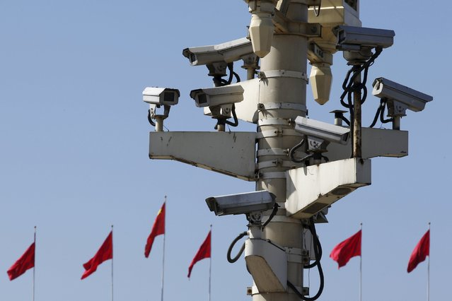 Security cameras in Tiananmen square are seen in front of flags on the Great Hall of the People where the National People's Congress (NPC) is being held, in Beijing, China, March 11, 2016. (Photo by Kim Kyung-Hoon/Reuters)