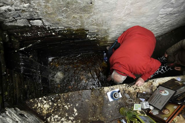 A man bends down to drink water from the holy well of St. Brigid on a Pattern Day pilgrimage to St. Brigid in Liscannor, Ireland February 1, 2017. (Photo by Clodagh Kilcoyne/Reuters)