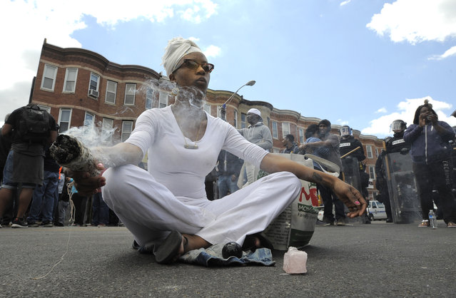 Shawna Murray-Browne sits in a street in Baltimore, Tuesday, April 28, 2015. Maryland's governor vowed there would be no repeat of the looting, arson and vandalism that erupted Monday in some of the city's poorest neighborhoods. (Photo by Lloyd Fox/The Baltimore Sun via AP Photo)