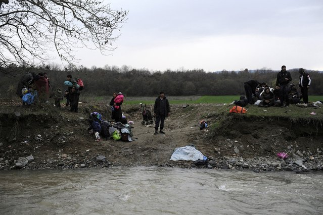 Migrants stand next to a river they waded as they look for a way to cross the Greek-Macedonian border, near the village of Idomeni, Greece, March 14, 2016. (Photo by Alexandros Avramidis/Reuters)