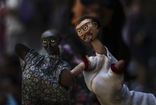 In this March 24, 2019 photo, a puppeteer presents his hand puppets during an event at the National Culture Museum in Mexico City. The event was held in honor of World Puppetry Day, observed earlier in the week on March 21. (Photo by Marco Ugarte/AP Photo)