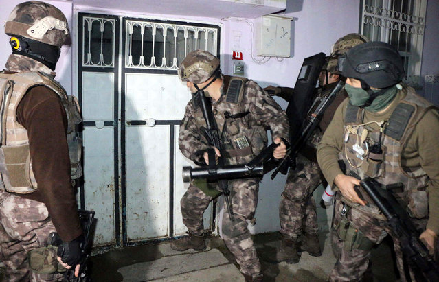 Turkish anti-terrorism police break a door during an operation to arrest people over alleged links to the Islamic State group, in Adiyaman, southeastern Turkey, early Sunday, February 5, 2017. Turkey's state-run agency says anti-terrorism police have detained more than 400 people in simultaneous police operations that spanned several cities, including Istanbul and Gaziantep near the border with Syria, according to the report. (Photo by Mahir Alan/Dha-Depo Photos via AP Photo)