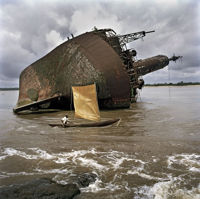 A fisherman passes the wreck of an old ship off the port of Greenville, Liberia, September 2005. Liberia is scattered with boat wrecks owing to the 14 year civil war. (Photo by Tim Hetherington/Magnum Photos)