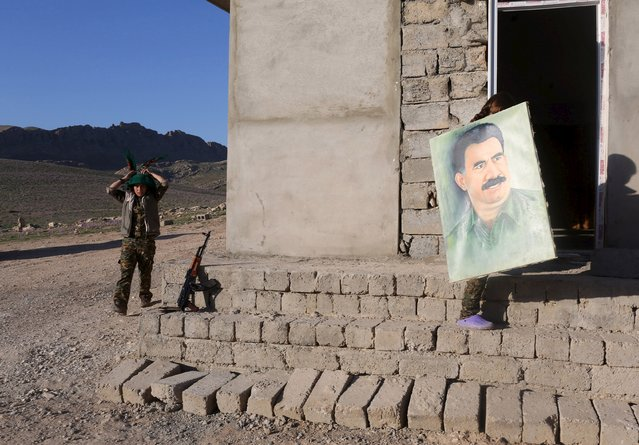 A female Kurdistan Workers Party (PKK) fighter adjusts her scarf while another carries a picture of jailed Kurdish militant leader Abdullah Ocalan at their base in Sinjar March 11, 2015. (Photo by Asmaa Waguih/Reuters)