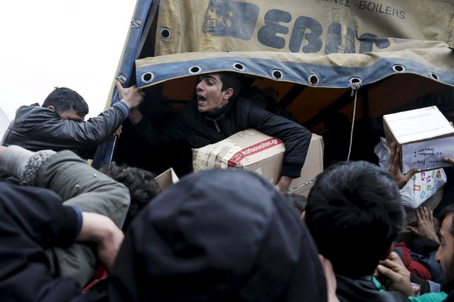 A young man (C) shouts as refugees and migrants grab goods donated by volunteers from a truck at a makeshift camp at the Greek-Macedonian border, near the village of Idomeni, Greece March 16, 2016. (Photo by Alkis Konstantinidis/Reuters)