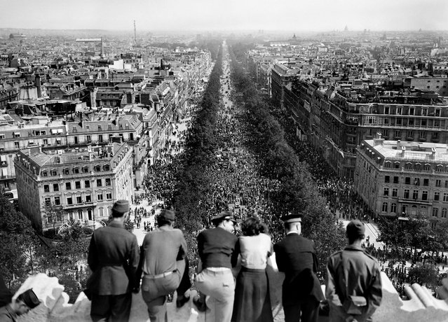 Picture dated of May 8, 1945 showing people looking at the crowded Champs Elysees Avenue from the Triumphal Arch (Arc de Triomphe) as Parisians gathered in the streets of Paris to celebrate the unconditionnal German capitulation at the end of the second World War. (Photo by AFP/Getty Images)