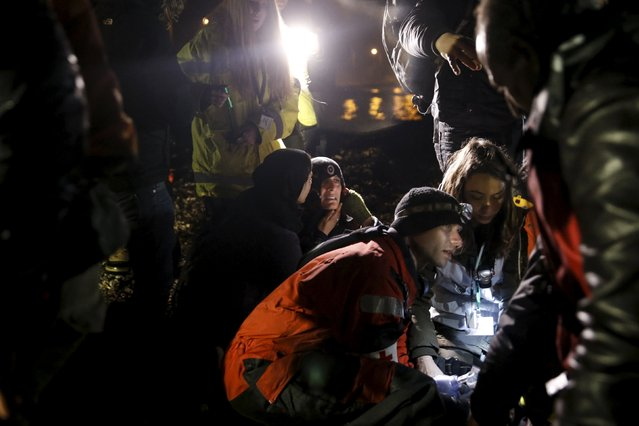 A refugee (C) reacts as rescuers try to revive an unconscious refugee after arriving on a dinghy on the shore near the city of Mytilene on the Greek island of Lesbos, March 20, 2016. The two men in this group of arrivals who were found unconscious were taken to hospital and were later pronounced dead by hospital authorities in Mytilene. Hospital authorities said they were both Syrians. (Photo by Alkis Konstantinidis/Reuters)