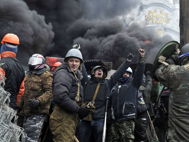 Protesters cheer while they managed to break police blockade in Kiev, on February 20, 2014. (Photo by Louisa Gouliamaki/AFP Photo)