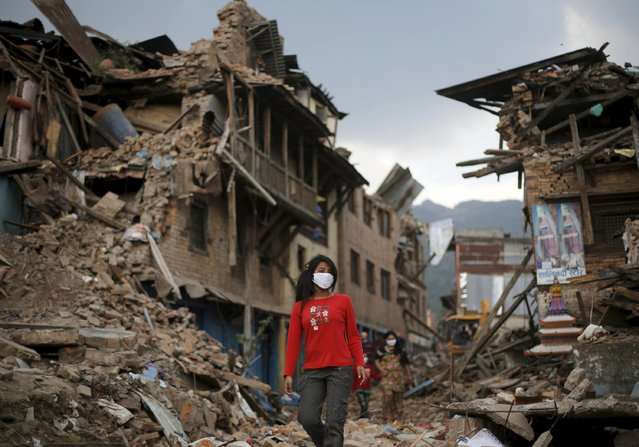 Earthquake victims walk along a street next to collapsed houses in Sankhu, on the outskirts of Kathmandu, May 2, 2015. Bureaucracy at Kathmandu airport was holding up vital relief supplies for survivors of the April 25 earthquake in Nepal as the death toll from the disaster passed 6,600. (Photo by Adnan Abidi/Reuters)