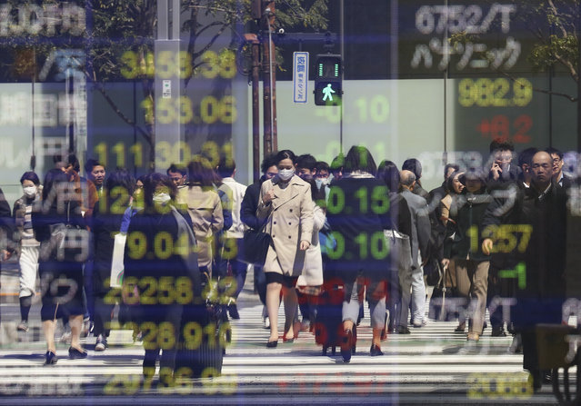 People are reflected on the electronic board of a securities firm in Tokyo, Tuesday, April 2, 2019. Asian stock prices followed Wall Street higher on Tuesday on encouraging global economic data. (Photo by Koji Sasahara/AP Photo)