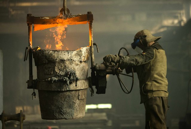 A worker operates a barrel with molten iron at an iron foundry in Bobruisk, southeast of Minsk, March 11, 2015. (Photo by Vasily Fedosenko/Reuters)