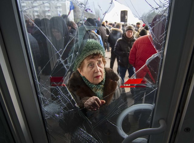 A woman looks through a damaged entrance door as pro-Russian demonstrators hold a rally outside the regional government building in Donetsk, March 3, 2014. Pro-Russian demonstrators occupied the first floor of the regional government building in east Ukraine's city of Donetsk on Monday, the latest in days of rallies that Kiev says are organised by Moscow as a pretext to invade. (Photo by Reuters/Stringer)