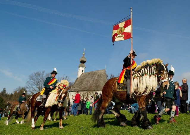 """Performers in traditional costumes ride decorated horses for the traditional """"Georgiritts"""" on Easter Monday in Traunstein, Germany, 28 March 2016. One of the largest horses pilgrimages takes in Bavaria every year in honour of St.George. (Photo by Angelika Warmuth/EPA)"""