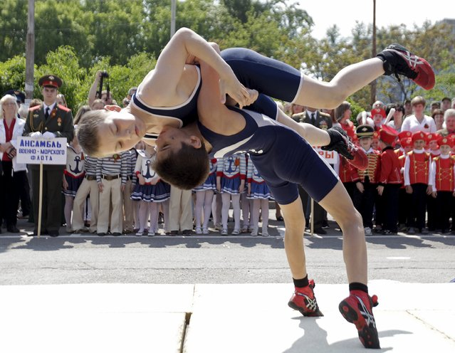 Young wrestlers perform as children gather in the background during the so-called parade of children's troops in Rostov-on-Don, southern Russia, May 14, 2015. (Photo by Eduard Korniyenko/Reuters)