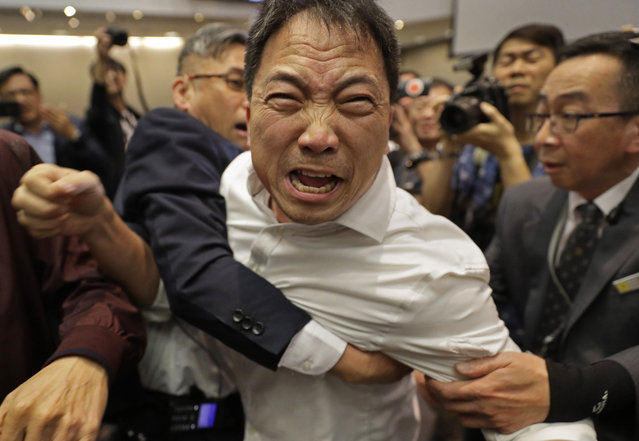 Pro-democracy lawmaker Wu Chi-wai, center, scuffles with security guards at Legislative Council in Hong Kong, Saturday, May 11, 2019. Hong Kong's legislative assembly descended into chaos Saturday as lawmakers for and against controversial amendments to the territory's extradition law clashed over access to the chamber. (Photo by Vincent Yu/AP Photo)