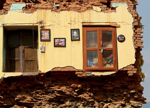 Framed pictures are seen hanging from the wall of a house damaged by earthquakes in Sindhupalchowk district, Nepal, May 13, 2015. (Photo by Ahmad Masood/Reuters)