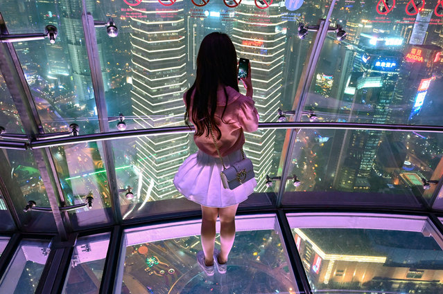 A young woman takes pictures of the city with her mobile phone, from the glass-floor observation platform, in the Oriental Pearl Tower, in the financial district of Shanghai, on May 9, 2019. (Photo by Hector Retamal/AFP Photo)
