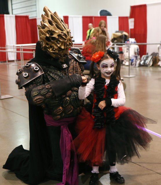 Rylee Donovan, dressed as Harley Quinn fist bumps Thomas Spanos as Darth Bane at the Motor City Comic Con at the Suburban Collection Showcase, Friday, May 15, 2015, in Novi, Mich. The three-day pop-culture extravaganza will welcome dozens of celebrities from the worlds of TV, film and beyond as well as thousands of fans. (Photo by Carlos Osorio/AP Photo)