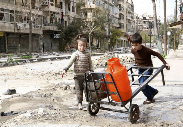 Children push a cart with water containers along a damaged street in old Aleppo March 11, 2014. The number of children affected by the civil war in Syria has more than doubled over the past year, with hundreds of thousands of young Syrians trapped in besieged parts of the country, the United Nations Children's Fund said. (Photo by Mahmoud Hebbo/Reuters)