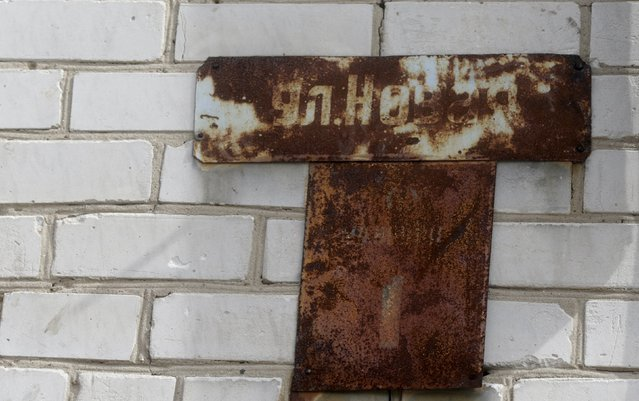 Rusty plate with the street name is seen on the wall of an abandoned apartment house in the ghost town of a former Soviet military radar station near Skrunda, Latvia, April 9, 2016. (Photo by Ints Kalnins/Reuters)