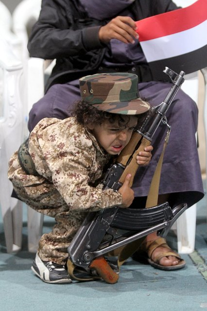 A boy tries to hold a rifle while attending celebrations marking the 25th anniversary of Yemen's unification with his brother in Sanaa May 23, 2015. (Photo by Mohamed al-Sayaghi/Reuters)