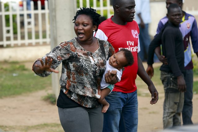 A woman carrying a baby argues with a man outside a petrol station of state-owned energy company Nigerian National Petroleum Corporation (NNPC) in Abuja, Nigeria May 25, 2015. (Photo by Afolabi Sotunde/Reuters)