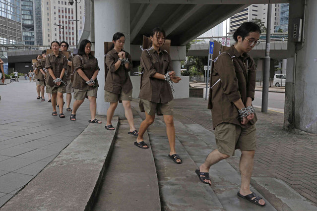 Students in chains march to protest the extradition bill in Hong Kong, Saturday, June 8, 2019. The extradition law has aroused concerns that this legislation would undermine the city's independent judicial system as it allows Hong Kong to hand over fugitives to the jurisdictions that the city doesn't currently have an extradition agreement with, including mainland China, where a fair trial might not be guaranteed. (Photo by Kin Cheung/AP Photo)