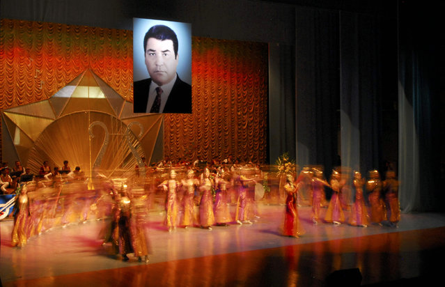 Dancers perform in a theatre at a new cultural centre in the Turkmen capital Ashgabat as a portrait of Turkmenistan's late leader Saparmurat Niyazov hangs in the centre, February 16, 2007. (Photo by Michael Steen/Reuters)