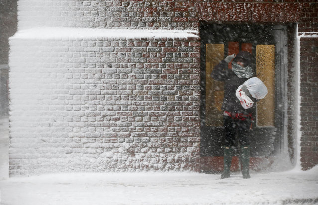 A person stands in the wind-driven snow during a winter storm Tuesday, March 14, 2017, in Boston. A powerful nor'easter hit the Northeast on Tuesday after a largely uneventful winter, dropping up to 2 feet of snow in some places, grounding thousands of flights and leading to school and work closures along the coast. (Photo by Michael Dwyer/AP Photo)