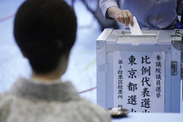 A voter casts a ballot in the upper house elections as a representative of a local election administration commission observes at a polling station in Tokyo Sunday, July 21, 2019. Voting started Sunday morning for the upper house elections where Japanese Prime Minister Shinzo Abe's ruling coalition is seen to retain majority, according to local media report. (Photo by Eugene Hoshiko/AP Photo)