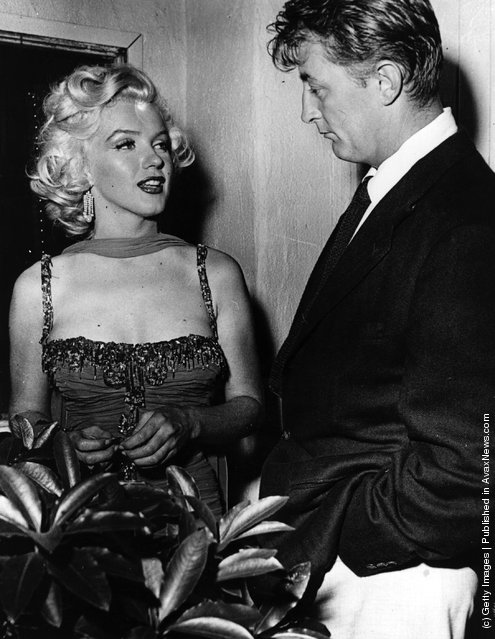 American actress Marilyn Monroe (1926 - 1962) with actor Robert Mitchum (1917 - 1997) at a Hollywood party