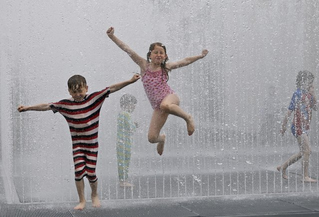 Lukas and Rosa enjoy the refreshing fountain  in Southbank, London, Wednesday, July 1, 2015. Britain is preparing itself for the hottest day in nine years Wednesday, with temperatures possibly rising to 35 Celsius (95 Fahrenheit) in London. (Photo by Frank Augstein/AP Photo)