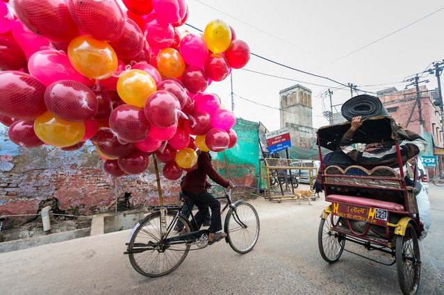 """""""Balloons Being Delivered In Agra"""". On a foggy day in Agra, India this moment quickly unfolded as I rode in alongside in a Rickshaw, The Balloons were amazing, having the man carrying carpet on the other rickshaw roof was just a bonus. Photo location: Agra, India. (Photo and caption by Chris McKillican/National Geographic Photo Contest)"""