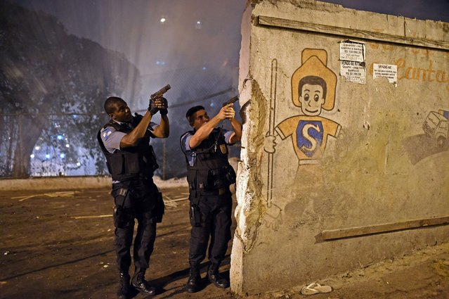 Rio de Janeiro's state military policemen aim their guns during a violent protest in a favela next to Copacabana, Rio de Janeiro on April 22, 2014. Violent protests broke out in Rio's landmark beachfront district, Copacabana, following the death of a resident last weekend during clashes with the Army in a nearby favela. (Photo by Christophe Simon/AFP Photo)