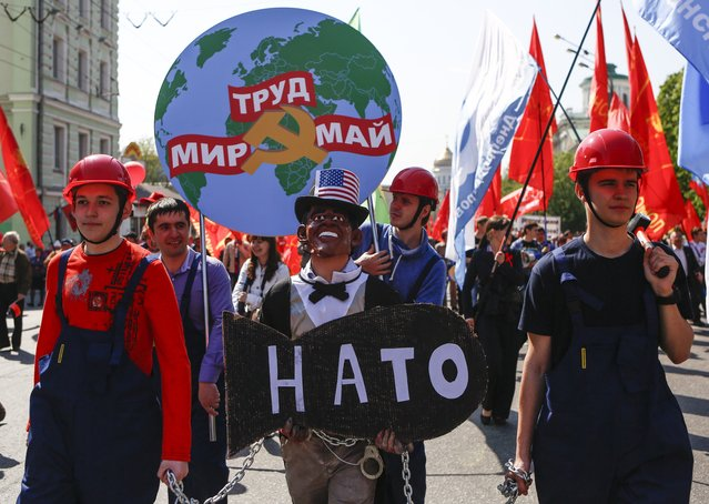 "People in helmets (left and right), dressed as Russian factories workers, hold a man wearing Barack Obama's mask with mock NATO's bomb in chains, as they take part in a Communists demonstration in downtown Moscow, Russia, Thursday, May, 1, 2014. Thousands of Communists, members of Russia's main political parties and opposition activists staged competing marches in Moscow and other cities Thursday marking the traditional May Day holiday. Poster at the background reads: ""Peace, Labour, May"". (Photo by Denis Tyrin/AP Photo)"