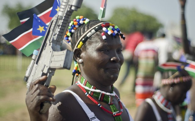 A South Sudanese woman wears the national flag and carries a mock gun as she attends an independence day ceremony in the capital Juba, South Sudan, Thursday, July 9, 2015. South Sudan marked four years of independence from Sudan on Thursday, but the celebrations were tempered by concerns about ongoing violence and the threat of famine. (Photo by Jason Patinkin/AP Photo)