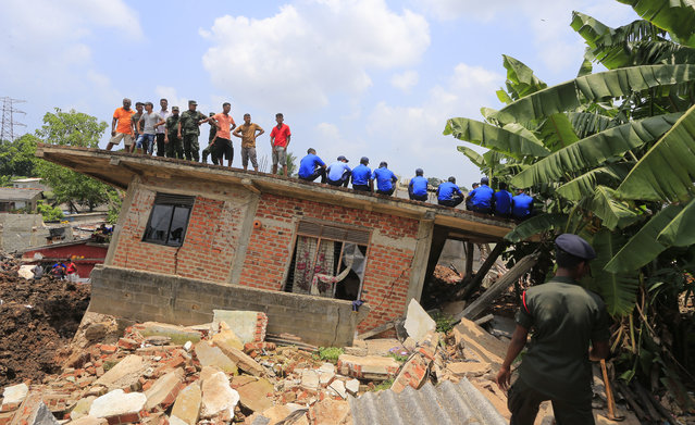 Sri Lankan military rescuers and onlookers rest on top of a damaged house at the site of a garbage dump collapse in Meetotamulla, on the outskirts of Colombo, Sri Lanka, Sunday, April 16, 2017. The death toll from the collapse of the massive garbage mound near Sri Lanka's capital rose to more than a dozen Sunday, and residents feared more victims could be buried underneath the debris. Maj. Gen. Sudantha Ranasinghe, who is heading the rescue efforts, said 78 houses were destroyed and more than 150 were damaged. (Photo by Eranga Jayawardena/AP Photo)