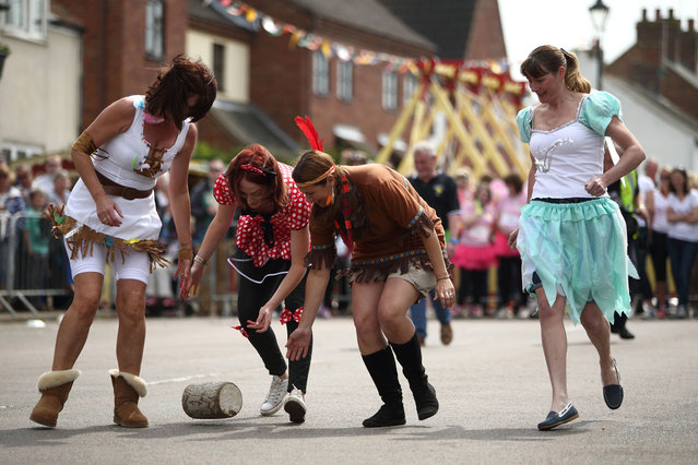 "A team roll a wooden ""cheese"" during the Stilton Village Festival cheese rolling competition on May 5, 2014 in Stilton, England. The Stilton annual cheese rolling competition, which is held annually on every May Day Bank Holiday involves teams of four competing against each other by rolling cheese down the High Street to be crowned the ""Stilton Cheese Rolling Champions"". (Photo by Jordan Mansfield/Getty Images)"