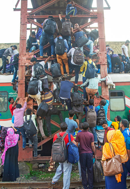 Bangladeshi people climb into the roof of an overcrowded train as they travel to celebrate Eid with family in their villages, at the Kamlapur Railway Station in Dhaka, Bangladesh, 03 June 2019. (Photo by Monirul Alam/EPA/EFE)